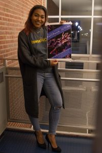 student holding danse macabre poster