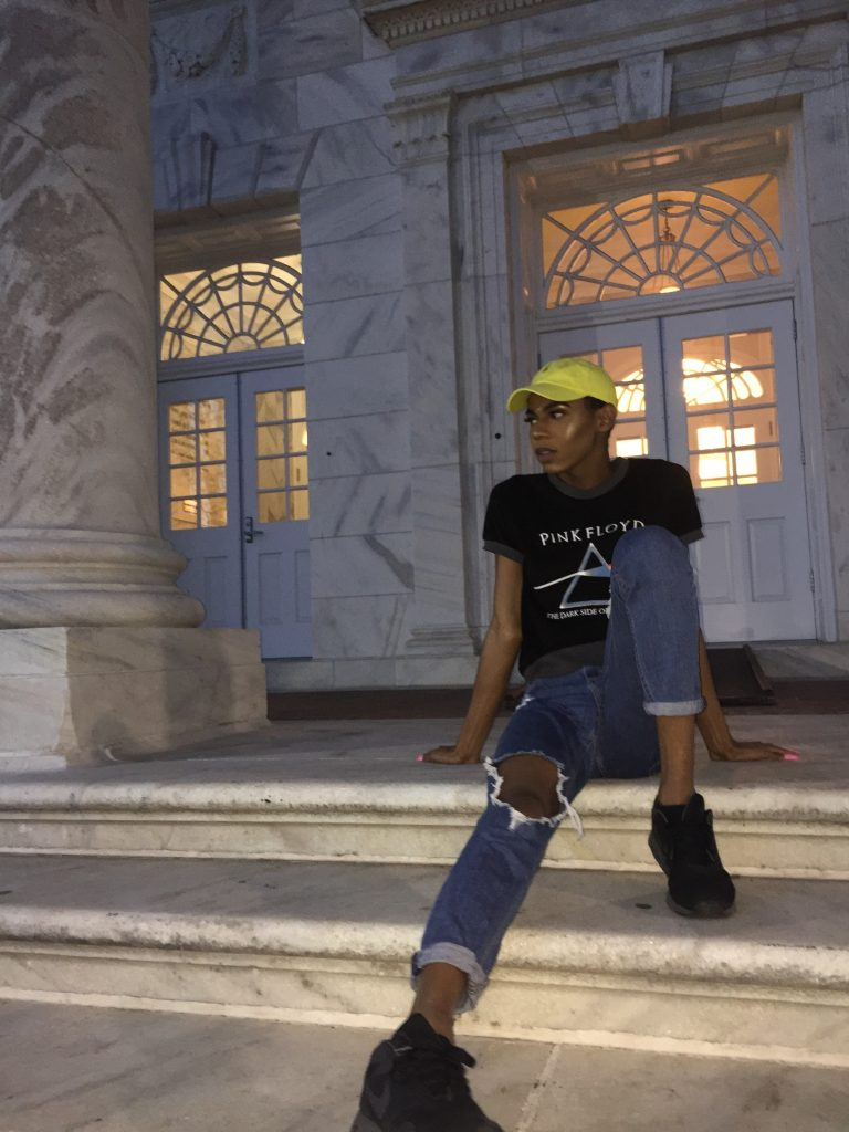 Divine Coleman sits on the steps of Bunce Hall