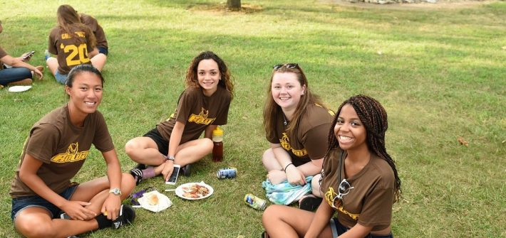 four girls wearing brown Rowan t-shirts sit on the grass