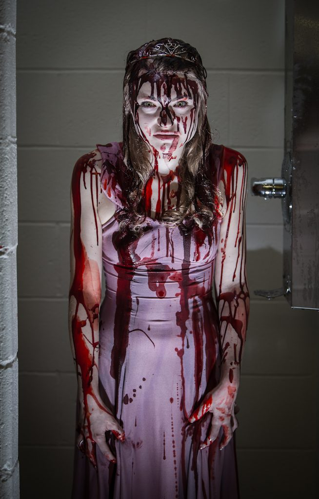 bloodied actress in a shower stall for Carrie: The Musical