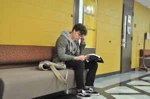 Greg sits on a bench inside of Robinson Hall
