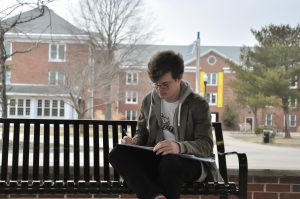 Greg sits on a bench, writing in a notepad, outside of a residence hall