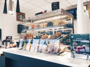 Starbucks counter selling assorted sweets and coffee
