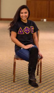 student in ballroom with greek life letters