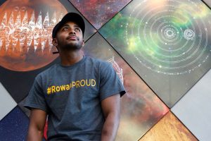 Sha stands in a gray Rowan Proud tshirt, in front of artwork