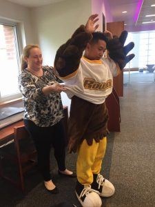 Mascot Whoo RU stands with hands in the air as Cristin helps to pull the oversized shirt off his head.
