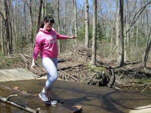Brianna balances while crossing water at a park