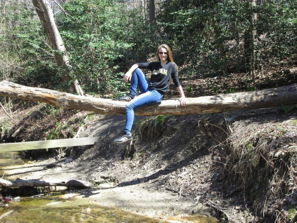 Kelly sits on a fallen tree over a creek