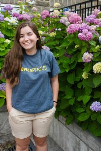 Annie wears a Rowan Proud tshirt in front of pink hydrangea plants