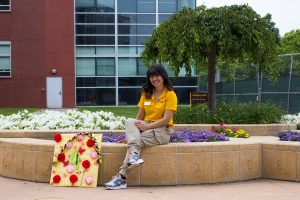 Female PROS member sitting in front of Science Hall.
