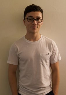 portrait of Anthony, wearing a white tshirt and black rimmed eyeglasses