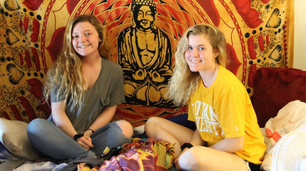 Freshman Kaylin Logan (left) with her friend Mallory Manz pose in front of Kaylin's tapestry.