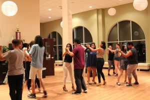 pairs of students interlock hands and dance the foxtrot in a line in the ballroom