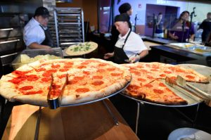 two pizza makers stand behind two fresh pizza pies