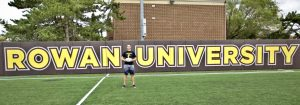 Ryan stands on rugby field with Rowan University sign behind him