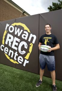 student holds a rugby ball while standing in front of a Rowan Rec Center sign