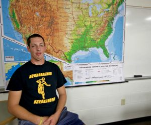 student sits in front of a map of the United States