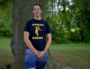 student stands in front of tree outside in Rowan's paths