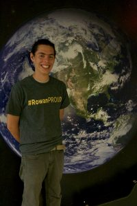 boy stands in front of an earth map with #ROWANproud shirt on