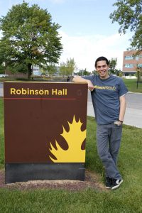 Tim is leaning on the Robinson Hall sign outside of the building