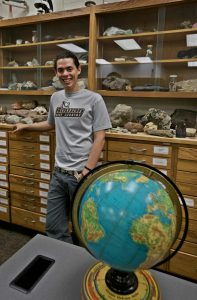Tim is standing in a geography room with a globe and rocks