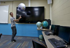 Tim is in computer lab throwing a globe blow- up ball in the air