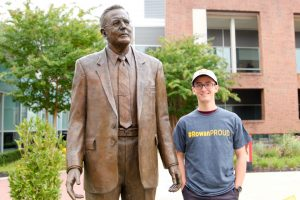 Kyle standing with the Mr. Rowan statue outside of Savitz Hall at Rowan University