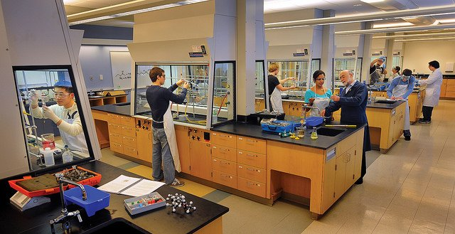 students handle lab materials in an organic chemistry class lab.