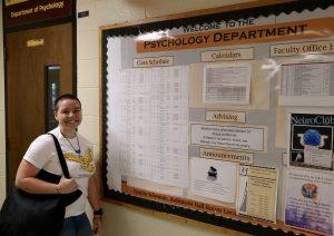 Jereca in front of Psychology bulletin board