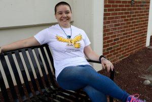 Jereca sitting on bench outside in Rowan tee