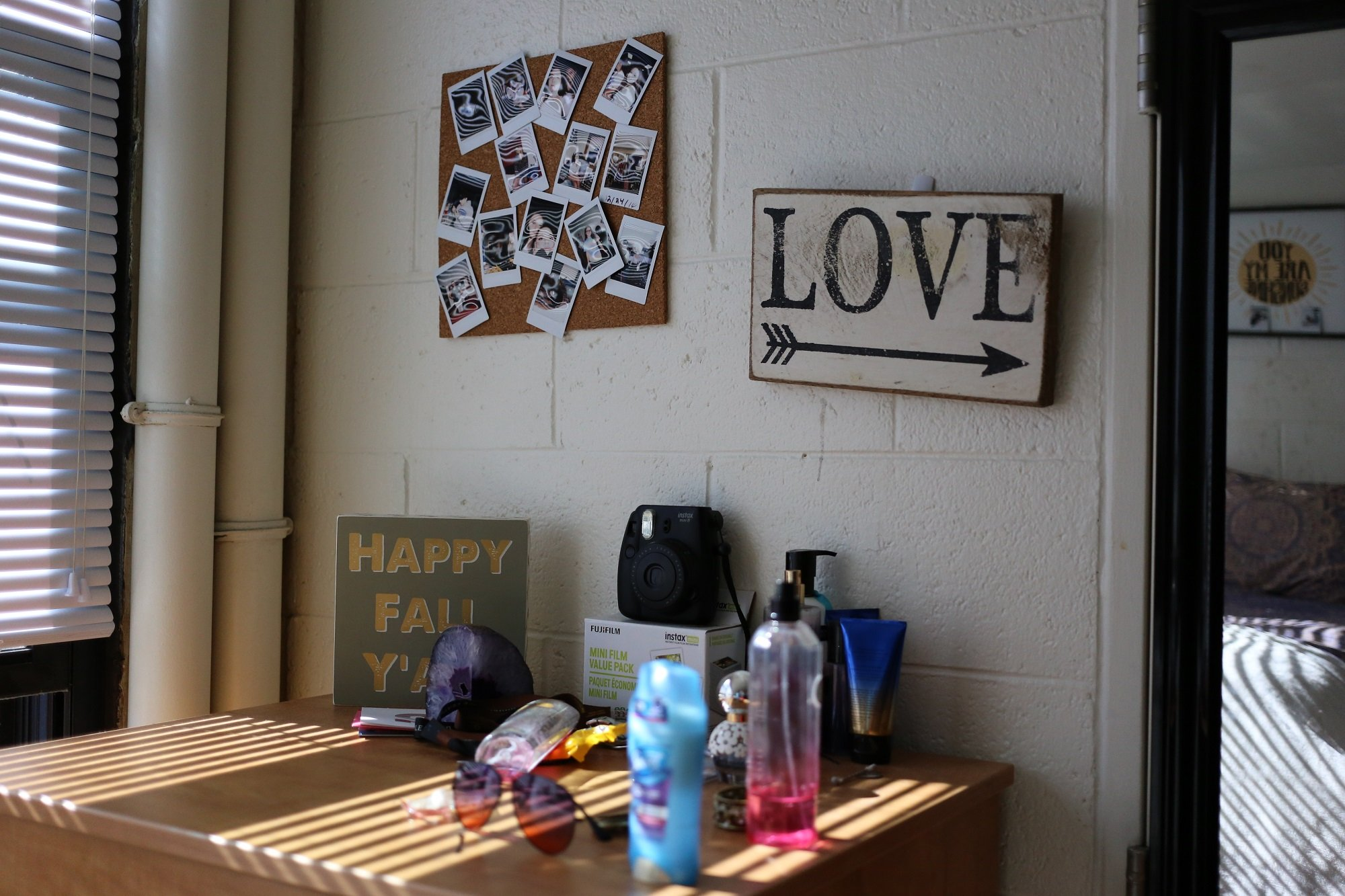 A photo of a bulletin board and printed sign on the dorm room wall of a student