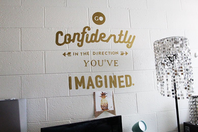 "A wall decal on Imani's wall that reads, ""Go confidently in the direction you've imagined,"""