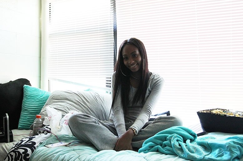 Imani sits on her bed and smiles.