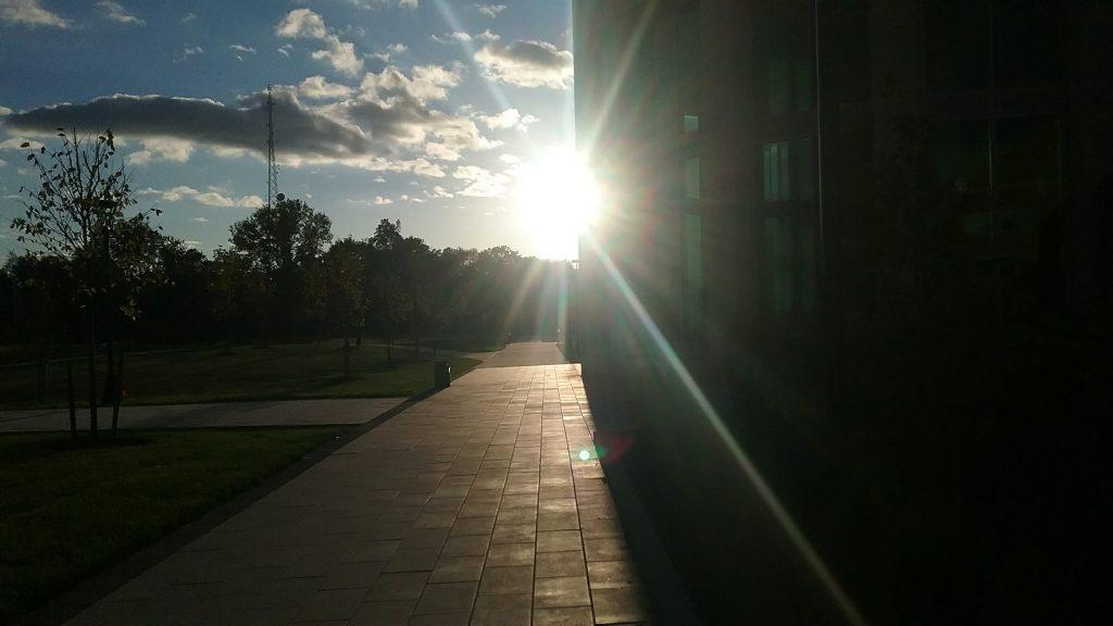 sunset peeking around the corner of a building at Rowan College at Burlington County, Rowan University partnership