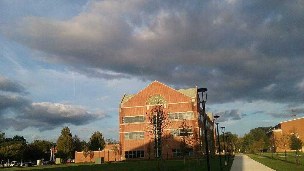 dark clouds and bright sun on a brick building at Rowan College at Burlington County, Rowan University partnership