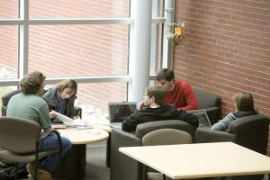 five students sit in lounge chairs in a lobby area at Rowan University to study