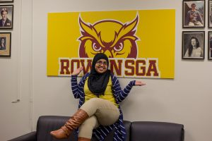 Student Government Association officer sits under an SGA sign with hands upward toward sign