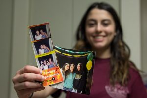 female student holds up Family Weekend photo and photo booth series
