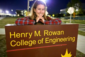 Alexa leaning on the engineering sign outside of Henry M Rowan Hall