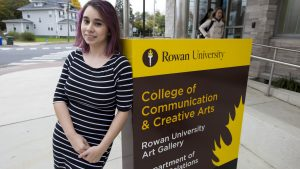 Erika at the College of Comm & Creative arts sign