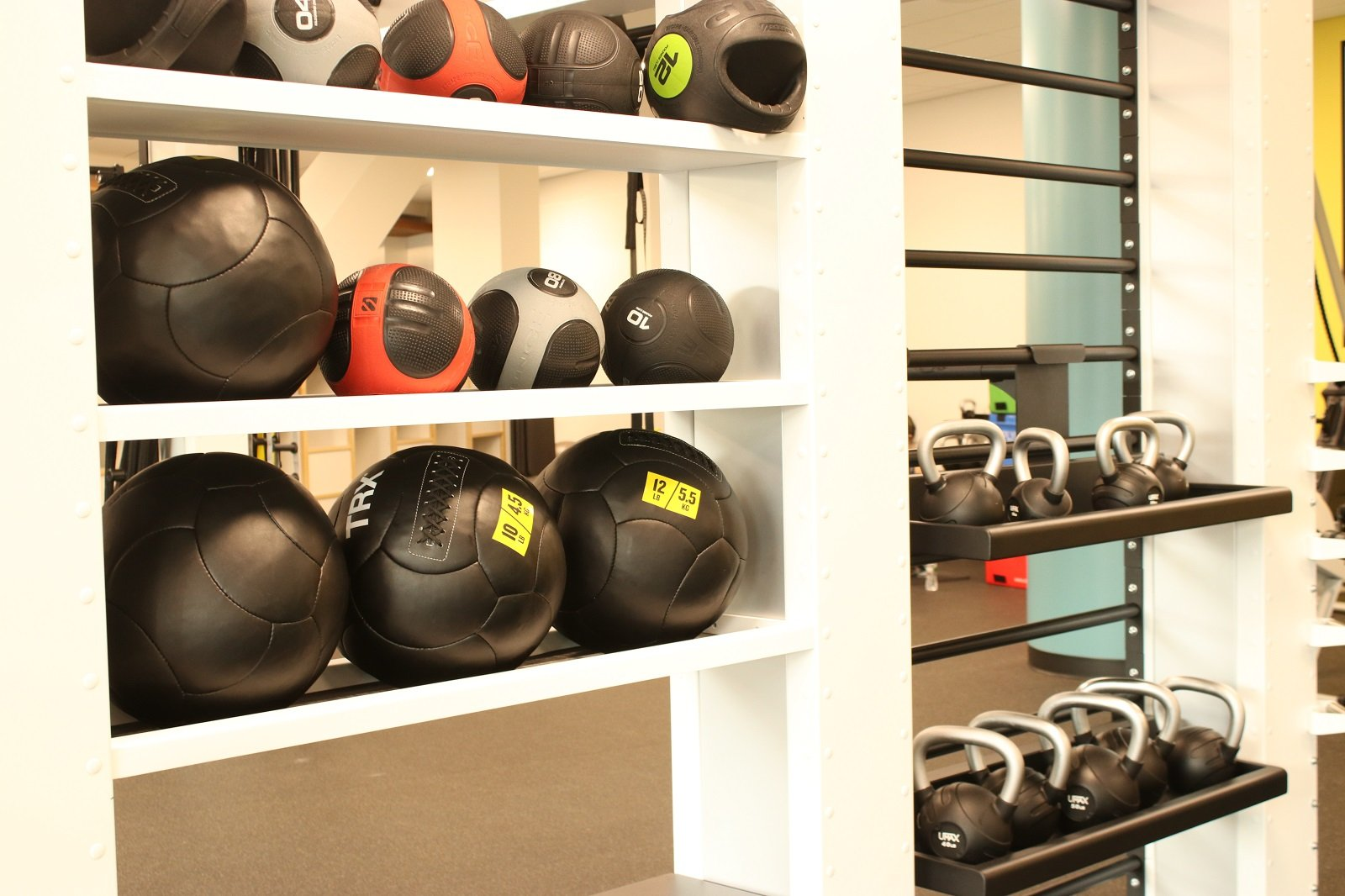 medicine balls and kettlebells on a shelf in the fitness center