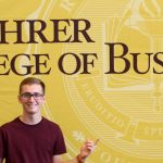Kyle in front of Rohrer College of Business sign