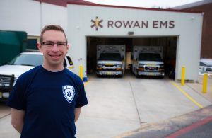 Rowan student Kevin standing outside Rowan EMS building in his EMS shirt on campus