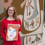 Rowan student Melissa holding her drawing outside Westby art building