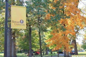 yellow Rowan flag banner with autumn leaves behind it