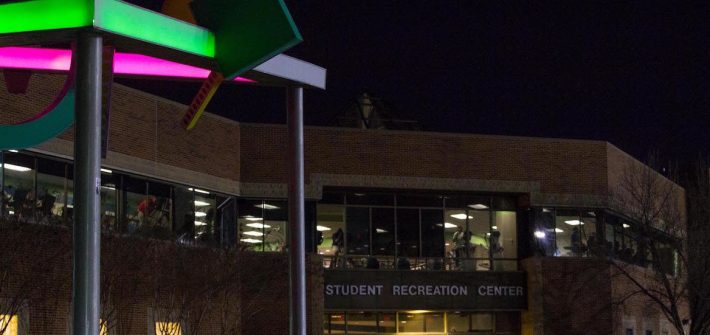 Front of Rec Center at night, with brightly illuminated abstract art in front