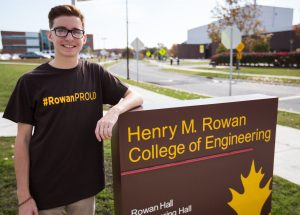 Rowan student Dylan pictured at Henry M. Rowan college of engineering sign outside the engineering building on campus