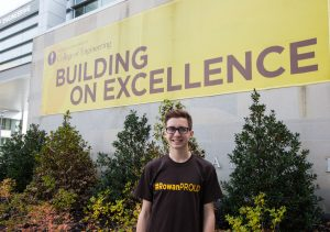 "Rowan student Dylan pictured at the Henry M. Rowan College of Engineering building ""Building on excellence"" sign"