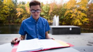 Rowan student Dylan studying outside Henry M. Rowan Engineering building at a fountain and lake