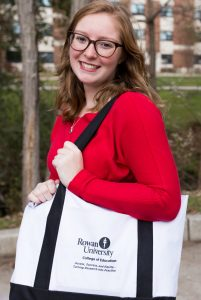 Rowan student Melissa with College of Education bag outside Student Center